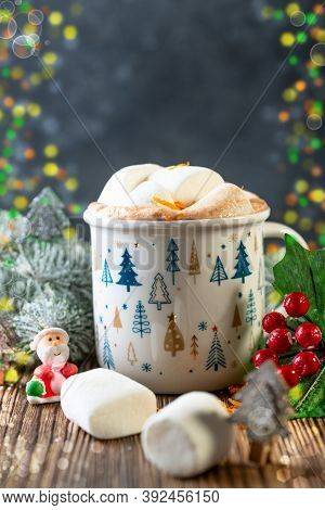 Mug Of Hot Chocolate With Marshmallows And Snowy Fir Branches On Wooden Table. Christmas Drink Conce