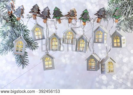 Christmas Background Of A Garland Of Lights In The Form Of Houses On Snowy Fir Branches On White Bac
