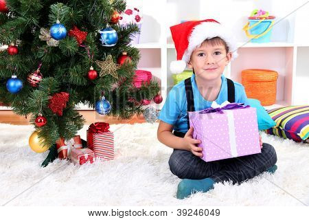 Child in Santa hat sits near Christmas tree with gift in hands