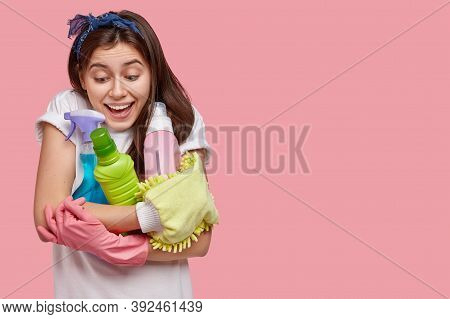 Studio Shot Of Joyful Young Housemaid Dressed In White T Shirt, Holds Cleaning Agents, Smiles Positi