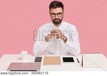 Horizontal Shot Of Self Assured Handsome Bearded Young Man In White Formal Shirt, Wears Transparent