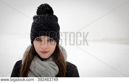 Outdoor Portrait Of Young Caucasian Girl With Long Brown Hair And Blue Eyes In Winter Hat, Scarf And