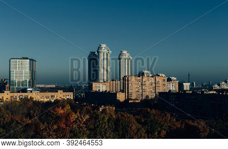 Urban Landscape With Old And New Housing In Morning Light With Hard Shadows And Blue Sky. In Foregro