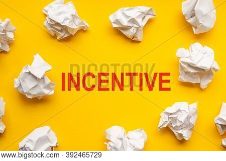 Incentive Text On Yellow Background With Copy Space. Crumpled Sheets Of Paper Lie Around. Business C