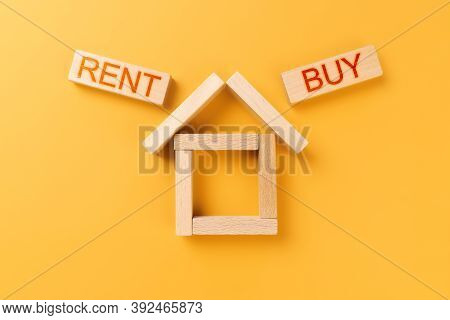 Rent Buy Home. House Made Of Wooden Cubes With The Words Rent And Buy On An Orange Background