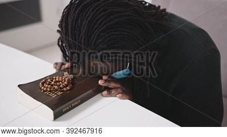 Black African Descent Man With Face Mask Praying On Holy Bible Book And Rosary. Seeking Hope In Reli