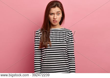 Indignant Dissatisfied Woman Raises Eyebrows, Has Surprised Expression, Wears Striped Clothes, Expre