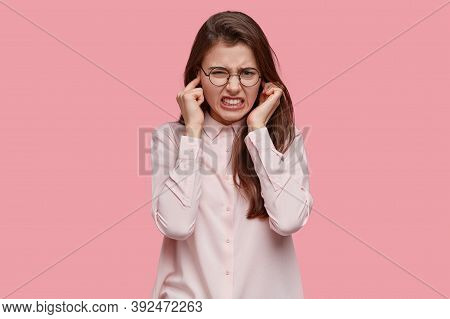 Frustrated Young Lady Plugs Ears, Clenches Teeth From Annoyance, Ignores Annoying Sound, Wears Trans