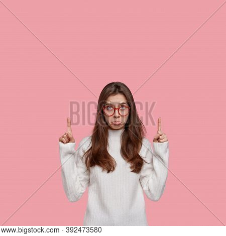 Unhappy Cute Woman Points With Fore Fingers Upwards, Disappointed By Something Negative, Dressed In