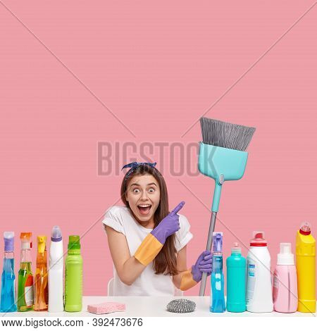 Vertical Shotof Pleased Merry Young Housewife Points At Broom With Satisfaction, Wears Protective Gl