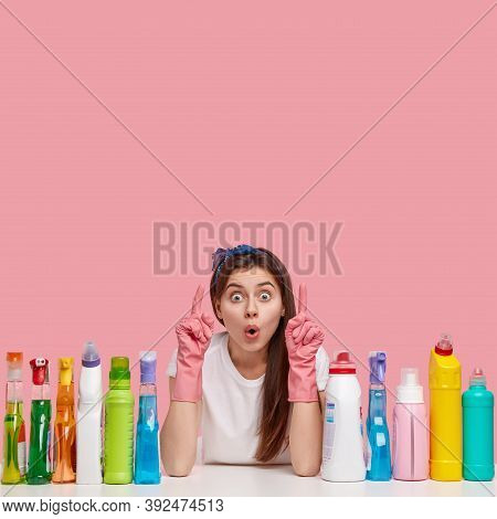 Shocked European Housemaid Has Scared Facial Expression, Dressed In Rubber Gloves, Demonstrates Some