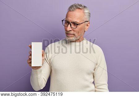 Headshot Of Handsome Wrinkled Bearded Senior Male In White Casual Jumper, Holds Little White Box Wit