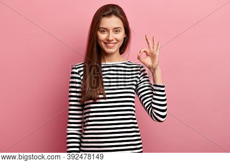 Image Of Young Attractive Lady Feels Happy, Makes Okay Gesture, Dressed In Casual Clothes, Has Long