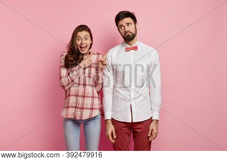 Half Length Portrait Of Happy Woman Indicates At Unsuccessful Man Who Has Dejected Facial Expression