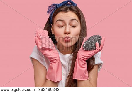 Photo Of Atractive Woman With Healthy Skin, Folded Lips, Closes Eyes, Wants To Kiss Someone, Carries