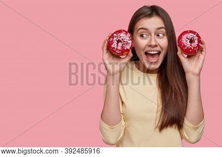 Joyful Youngster With Dark Hair, Carries Two Delicious Glazed Donuts, Opens Mouth Widely, Dressed In