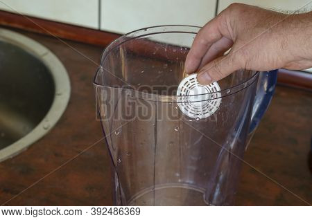 A Hand Lowers A Silicon Filter Into An Empty Water Jug. A Cartridge For Enriching Drinking Water Wit