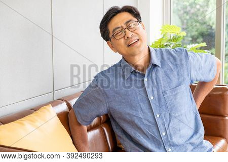 Indoor Shot Of Senior Asian Men Sit On The Sofa Couch And Touch His Back And Suffering From Back Pai