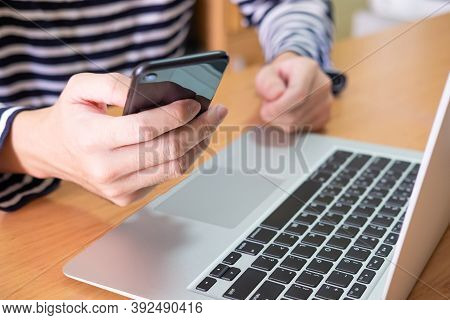 Men Hand Using Mobile Phone In Front Of His Computer Laptop On Wooden Table At Home. High Speed Inte