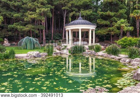 White Pavilion Near The Green Pond In The Garden With Reflection In The Summer Day. Alcove Architect