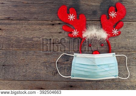 Deer Antlers In A Medical Mask On A Wooden Background. The Concept Of Christmas In The Face Of The C