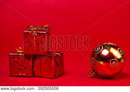 Christmas Decorations On A Red Background. Holiday Decorations. Three Red Gifts And A Red Christmas