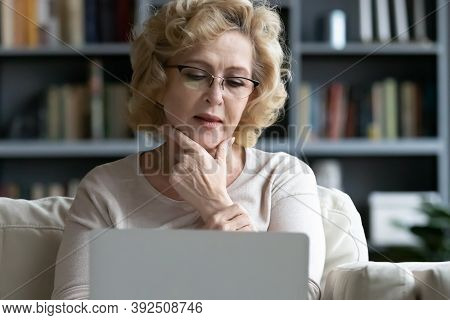 Thoughtful Elderly Woman Looking At Computer Screen.