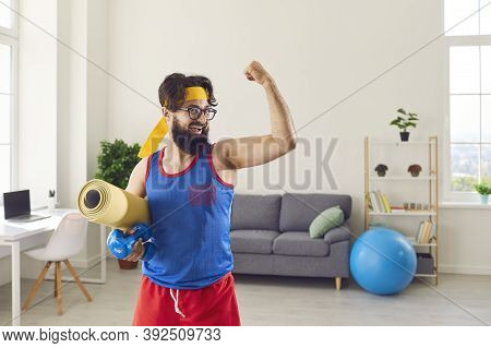 Funny Athlete Holding Gym Mat And Dumbbells And Showing His Weak Biceps After Sport Workout At Home