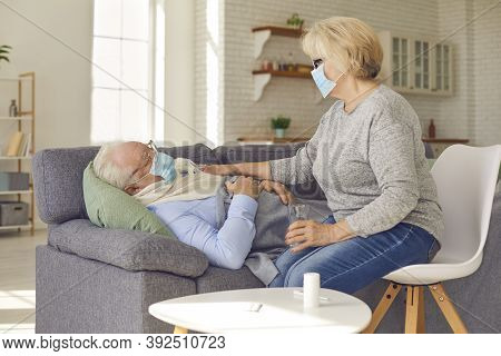 Senior Wife Taking Care Of Her Sick Husband Lying On Sofa Suffering From Flu Or Common Cold