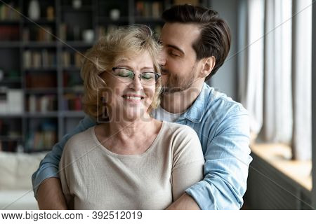Devoted Young Man Showing Care To Smiling Retired Old Mother.