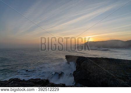 Huge Storm Surge Ocean Waves Crashing Onto Shore And Cliffs At Sunrise