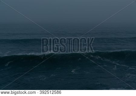 Detail View Of Large Waves Breaking In The Open Ocean At Night During A Tropical Storm