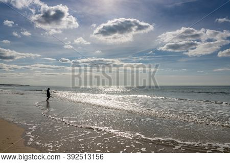 Woman In Silhouette In The Surf At A Wild And Empty Beach During A Beautiful Sunrise