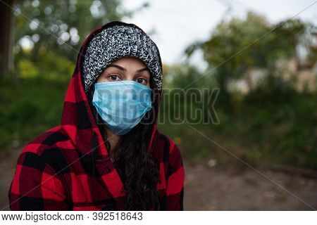 Young Depressed Homeless Woman With Hood And Protective Medicine Mask Against Coronavirus Or Covid-1