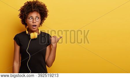 Studio Shot Of Astonished Black Woman Points Aside With Thumb, Has Thrilled Expression, Shocked To H