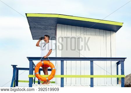 Male Lifeguard With Binocular On Watch Tower Against Blue Sky