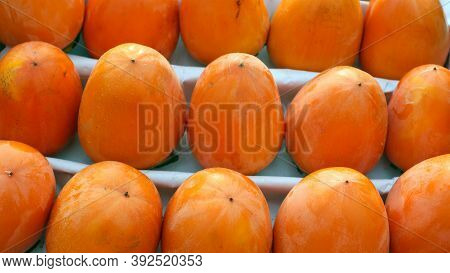 Fresh Ripe Persimmon In Autumn. Lots Of Bright Ripe Persimmons In A Box In A Row. Seasonal Autumn Fr