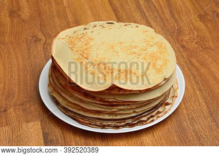 A Lot Of Pancakes Stacked On A Plate, Against The Background Of A Wooden Texture