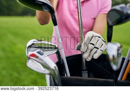 Female Player Choosing Clubs For The Game Of Golf