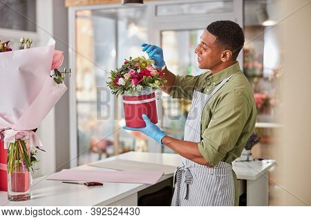 Flower Store Salesperson Arranging Roses In A Pot