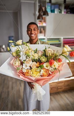 Delighted Multiethnic Florist Presenting A Flower Posy