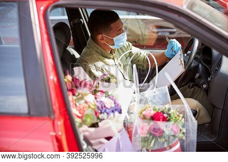 Florist Sitting In A Car With Notepad And Flowers