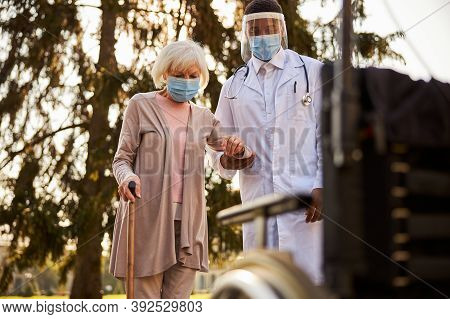 Cautious Doctor Leading An Aging Woman To A Wheelchair