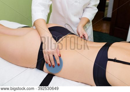 The Beautician Installs Electrodes To Myostimulation The Buttocks Of The Young Woman.