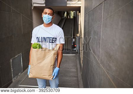 Glad Volunteer In A Face Mask With A Paper Bag
