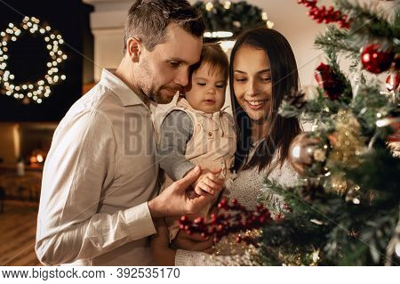 Young Family Greets The New Year And Christmas, Dad And Mom Hold Their Daughter In Their Arms And De