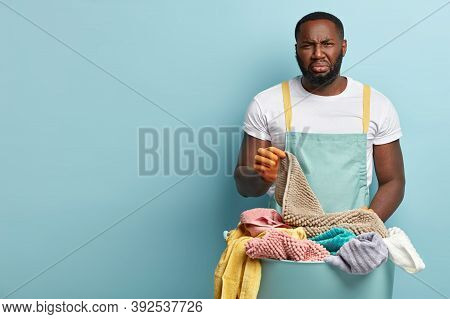 Dark Skinned Husband With Disgusting Facial Expression, Frowns Face Because Of Unpleasant Smell From
