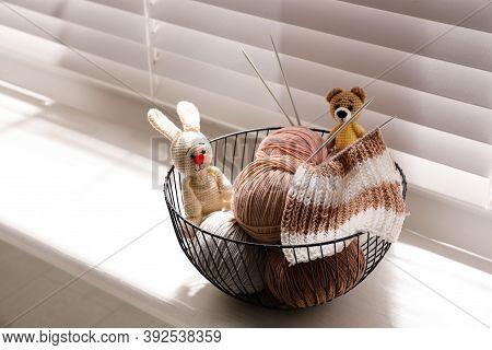 Yarn Balls, Knitting Needles And Cute Handmade Toys In Metal Basket On Window Sill Indoors. Creative