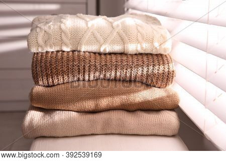 Stack Of Folded Warm Sweaters On Window Sill Indoors, Closeup