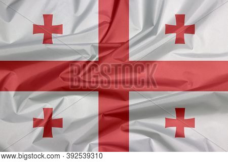 Fabric Flag Of Georgia. Crease Of Georgian Flag Background, White Rectangle, With A Large Red Cross.